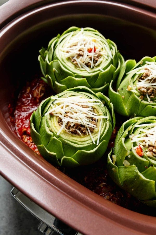 Four stuffed artichokes on top a layer of homemade marinara in a slow cooker