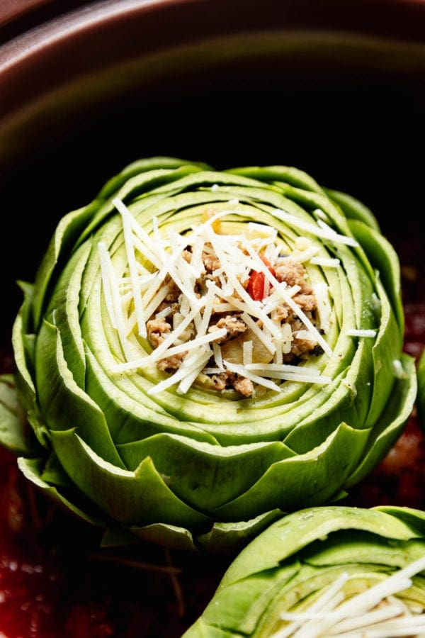 A fresh artichoke stuffed with Italian seasoned turkey and topped with mozzarella cheese in a slow cooker