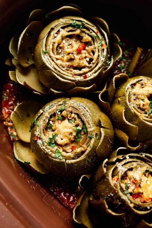 Freshly cooked Italian Stuffed Artichokes in homemade marinara sauce in a crockpot