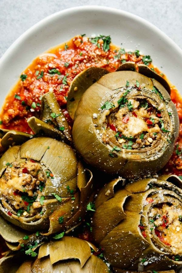 Three slow cooked Italian stuffed artichokes plated on top homemade marinara sauce on a white platter