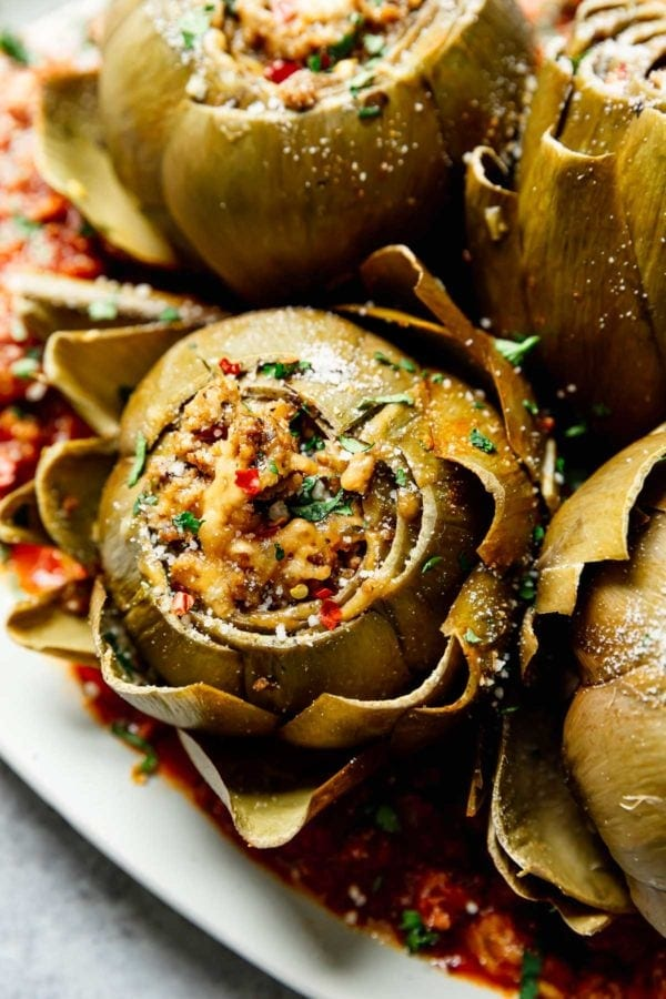 Close up of a stuffed artichoke topped with fresh herbs, peppers, and melted mozzarella cheese