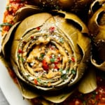 Italian Stuffed Artichokes in homemade marinara sauce on a white platter
