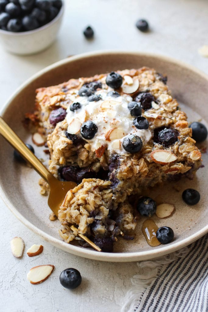Blueberry baked oatmeal in a shallow bowl with a forkful on creamy baked oatmeal on a gold fork