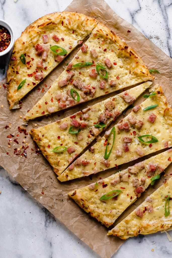 A breakfast pizza with a hash brown crust topped with sausage and scallions.