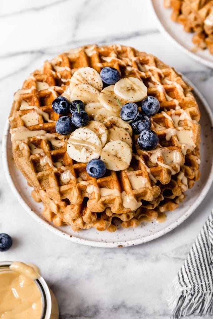 A stack of peanut butter banana waffles on a speckled plate topped with fresh bananas and blueberries