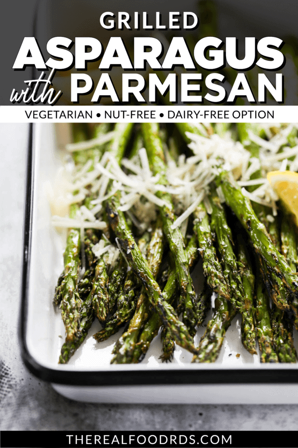 Close-up view of grilled asparagus in a grill pan topped with fresh parmesan and lemon wedges