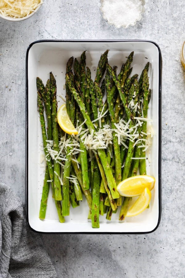 Freshly grilled asparagus spears in a grill pan topped with parmesan cheese and lemon wedges