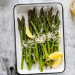 Fresh grilled asparagus in a grill pan topped with fresh parmesan and lemon wedges
