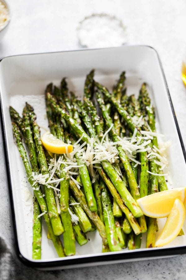 Grilled asparagus topped with fresh parmesan shreds and lemon wedges in a grill pan
