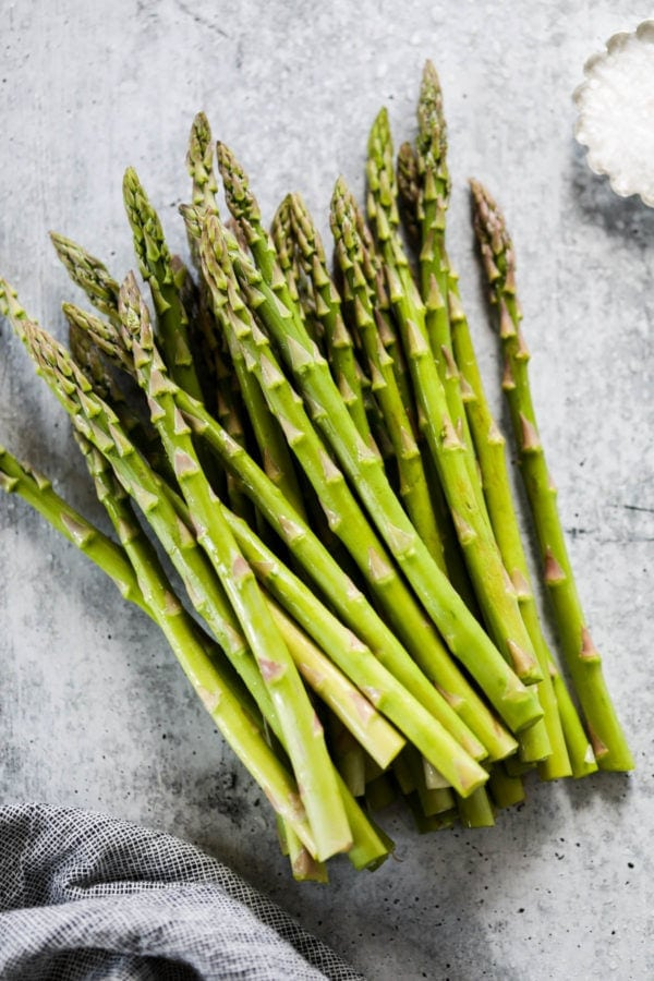A bunch of fresh cut asparagus stalks on a grey and white counter