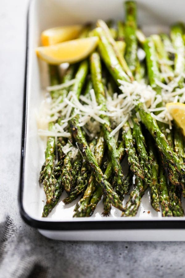 Close up view of grilled asparagus topped with fresh grated parmesan cheese and lemon wedges