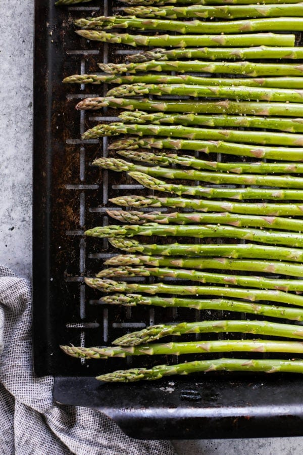 Asparagus stalks sprinkled with salt and pepper lined up on a grill grate ready for grilling
