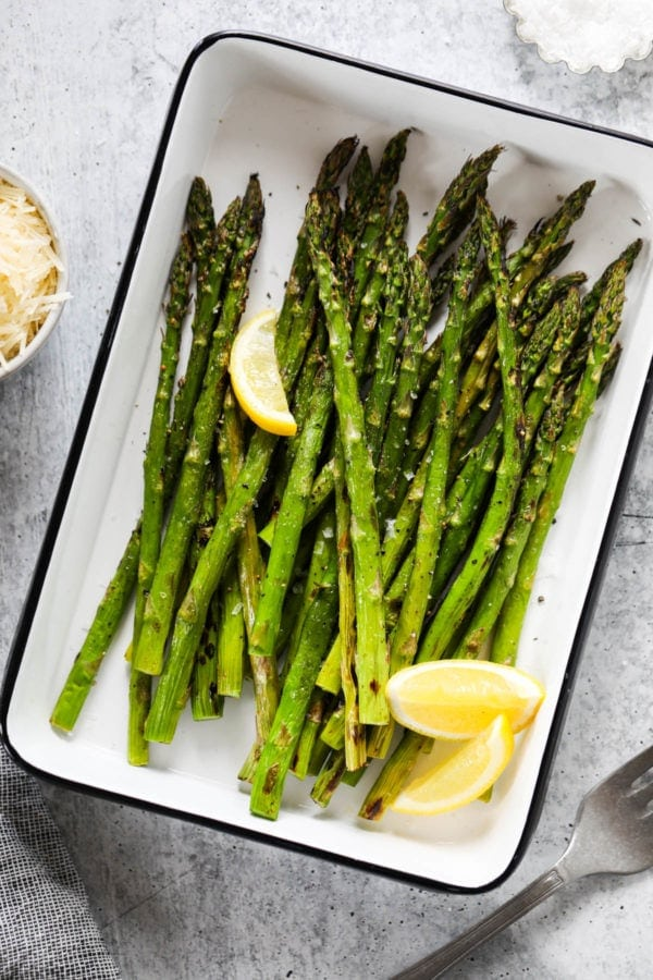 Grilled asparagus spears and lemon wedges topped with salt and pepper in a grill pan