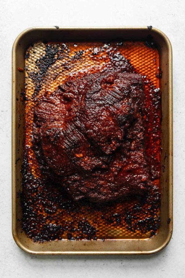 A broil-finished beef brisket on a deep baking sheet