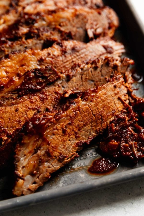 A close up view of a thin slice of juicy barbecue beef brisket on a silver baking tray