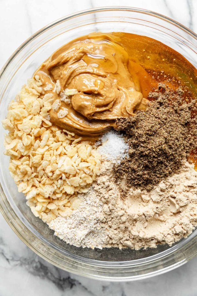 All ingredients for mini peanut butter protein bars in a glass mixing bowl ready to be mixed together.