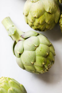 Close up view of an artichoke on a marble counter top