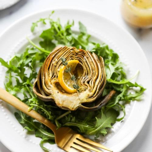 A roasted artichoke half on a bed of arugula topped with lemon shallot vinaigrette and a lemon slice.