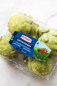 A package of four artichokes with a sticker for Ocean Mist Farms in the center