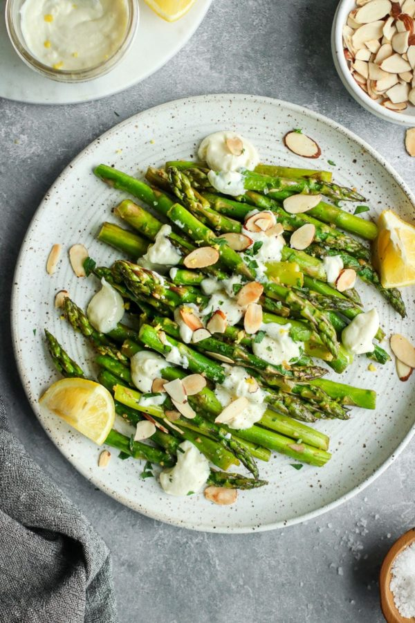 Sautéed asparagus on a speckled plate drizzled with goat cheese sauce and toasted almonds