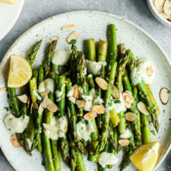 Sautéed asparagus topped with goat cheese sauce and toasted almonds on a speckled plate