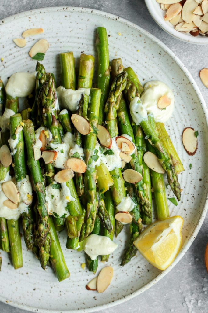 Sautéed Asparagus on a speckled white plate topped with lemon goat cheese sauce and toasted almonds.