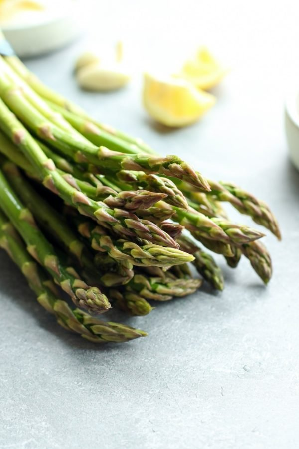Fresh asparagus spears catching the sunlight with lemon wedges in the background