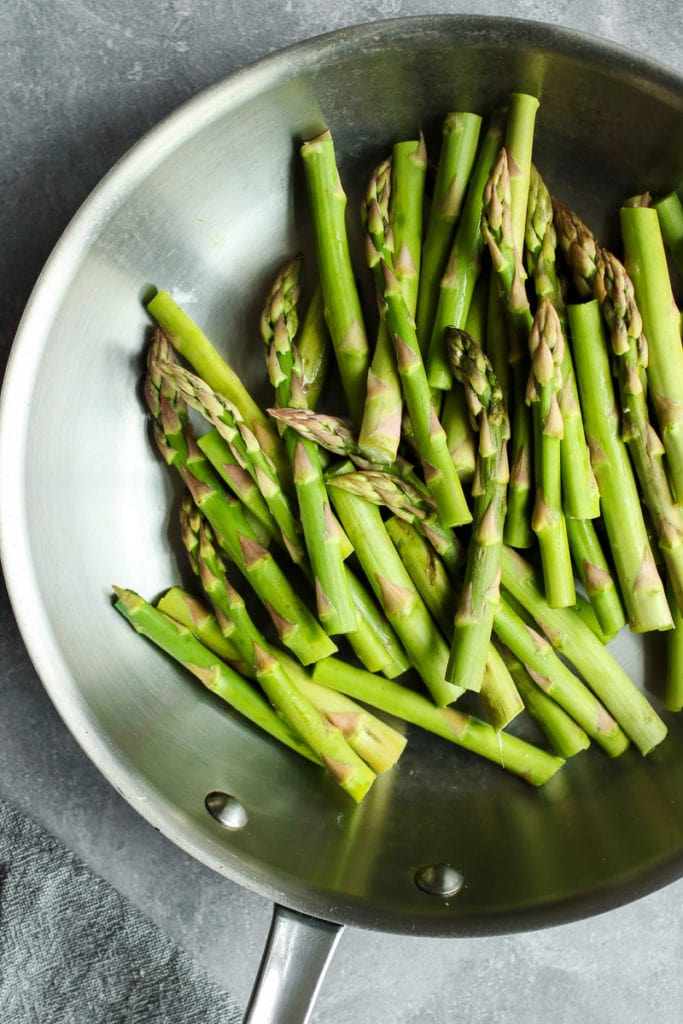 Fresh asparagus spears in a stainless steel pan.