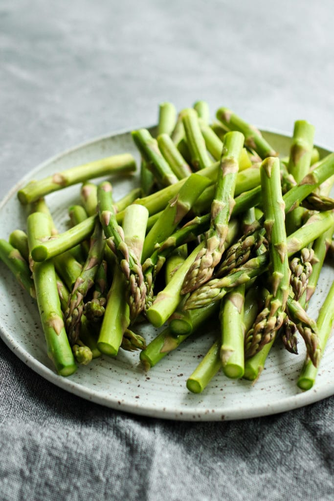 Fresh asparagus spears on a white speckled plate.