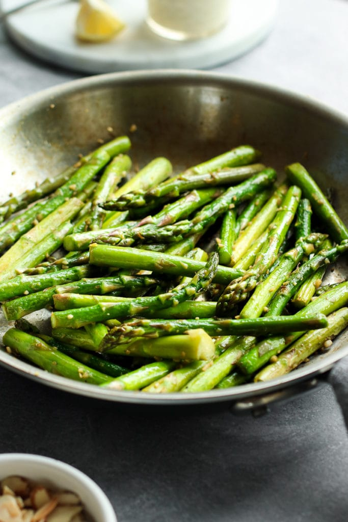 Sautéed Asparagus in a stainless steel pan.