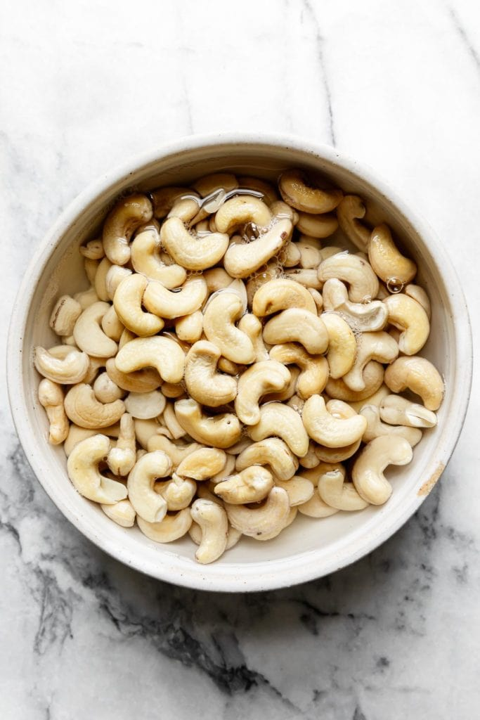 Raw cashews soaking in a bowl of water