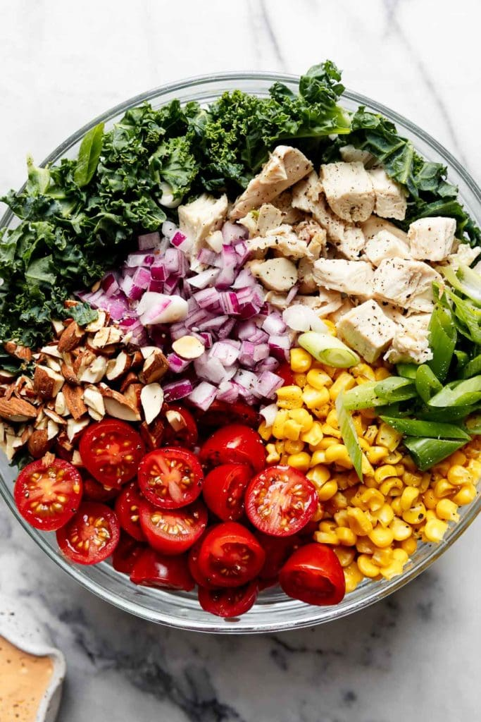 Ingredients of BBQ Chicken Salad in a clear mixing bowl.