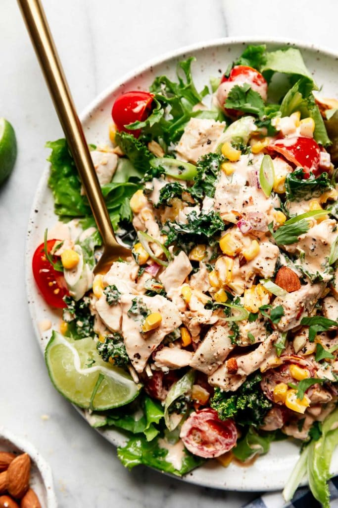Creamy BBQ Chicken Salad on a white plate served over a bed of greens.