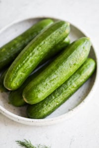 Small cucumbers on a speckled plate, washed and ready for slicing.