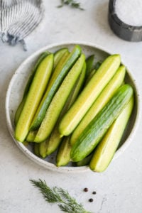 A small plate filled with cucumber spears ready for refrigerator pickles