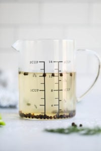 A measuring cup filled with brine for refrigerator pickles