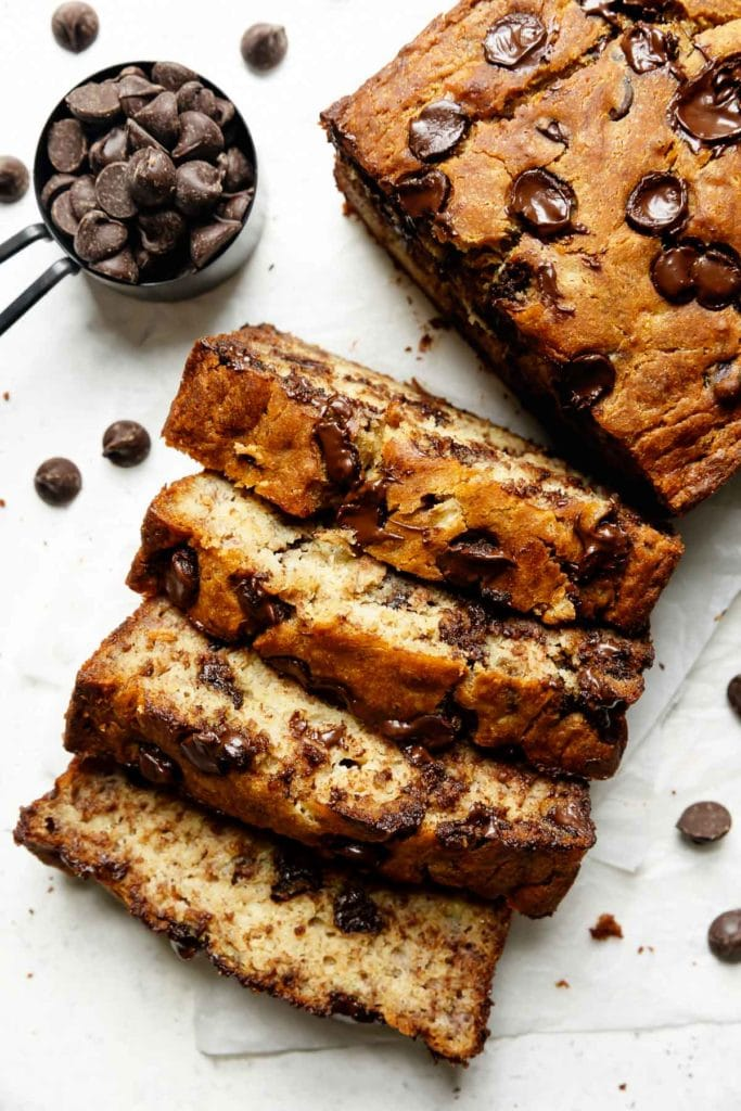 Thick slices of gluten-free banana bread topped with chocolate chips and baked to golden brown cut on a piece of parchment paper