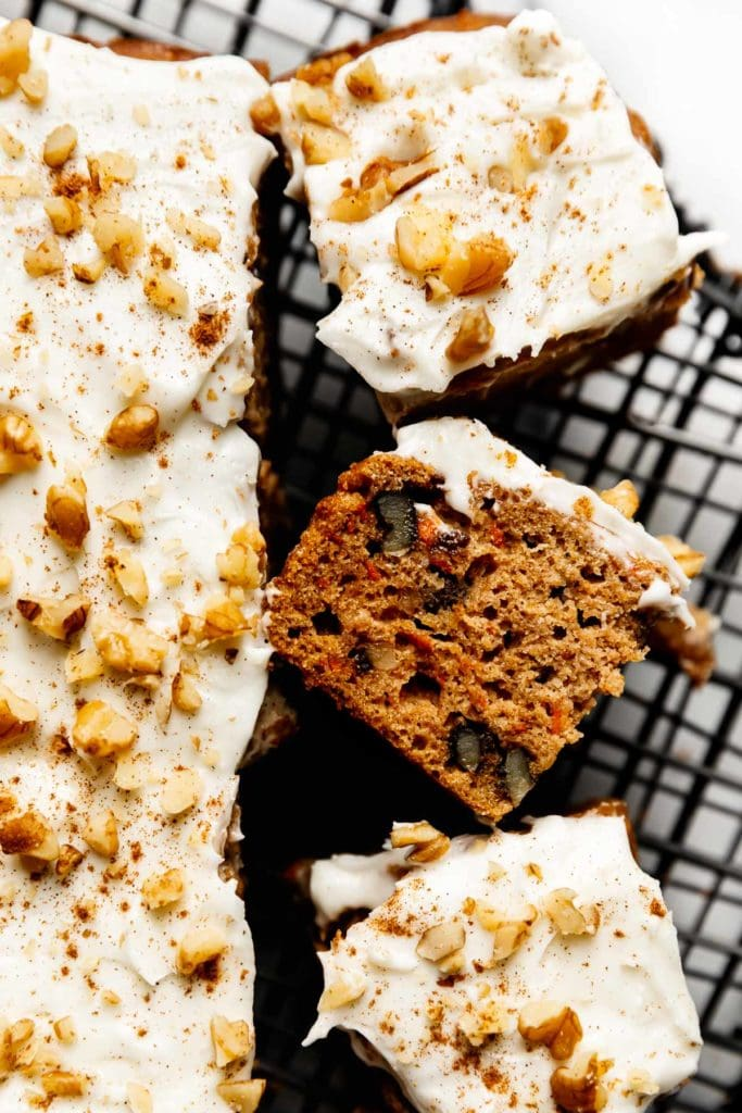 Healthy carrot cake bars topped with cream cheese frosting, cut into bars on a cooling rack