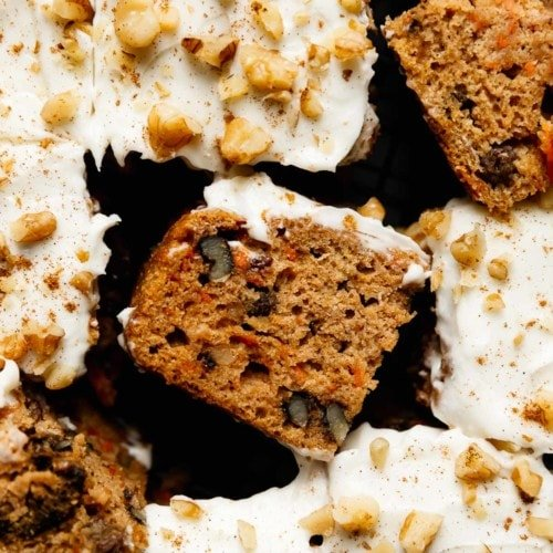 Healthy carrot cake bars topped with cream cheese frosting, cut into bars and styled on a cooling rack