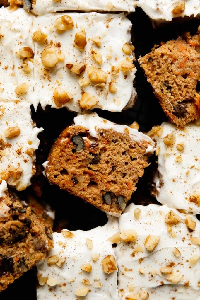 Healthy gluten-free carrot cake with cream cheese frosting cut into pieces and laying on their side to show texture