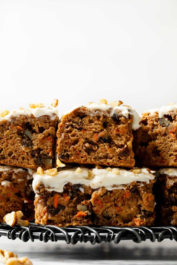 Gluten-free carrot cake bars with cream cheese frosting cut into bars and stacked on top of each other