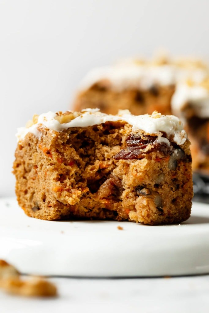 A close up view of a gluten-free carrot cake bar with a bite taken out to show texture