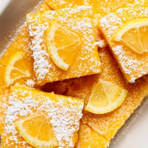 Lemon Bars sliced and topped with powdered sugar and lemon slices stacked in a white baking dish