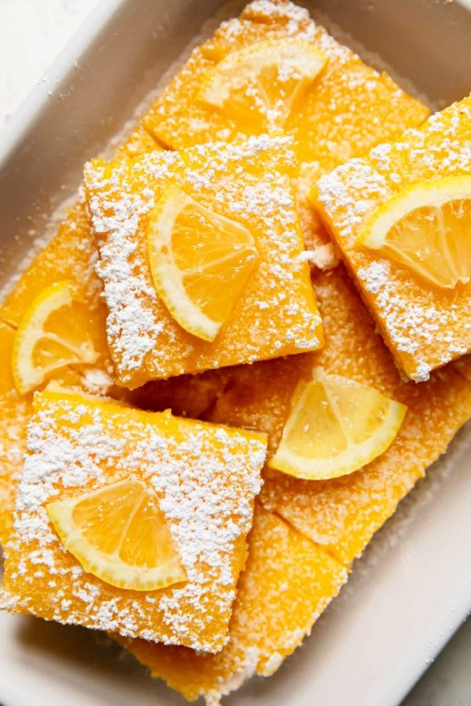 A tray of gluten-free lemon bars sprinkled with powdered sugar and a small lemon slice.