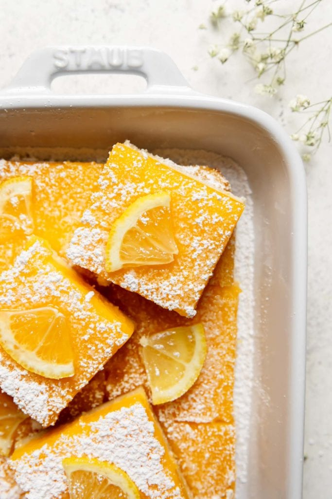 Lemon bars with a gluten-free shortbread crust cut into bars in a white baking dish