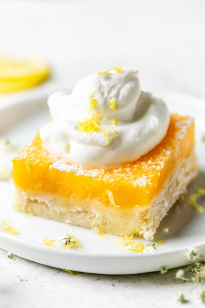 A single lemon bar with a gluten-free crust plated on a small round plate topped high with whipped cream and lemon zest