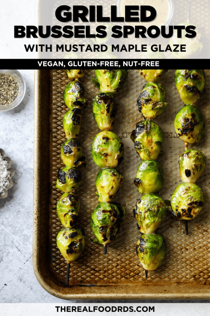 Grilled Brussels sprouts on skewers on a baking sheet with maple-mustard glaze drizzled on top