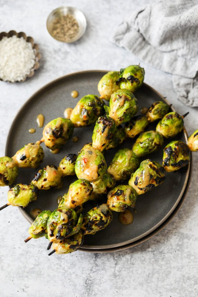 Grilled Brussels sprouts on skewers plated on a black plate with maple-mustard glaze drizzled on top.