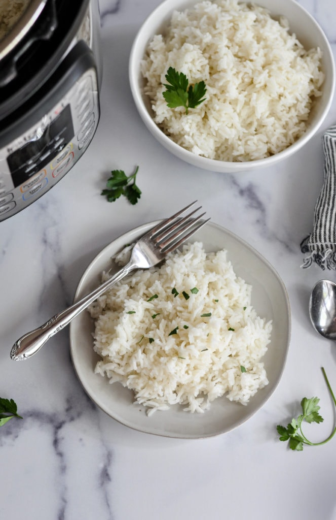 A plate of cooked jasmine rice and a serving bowl filled with jasmine rice near an instant pot.