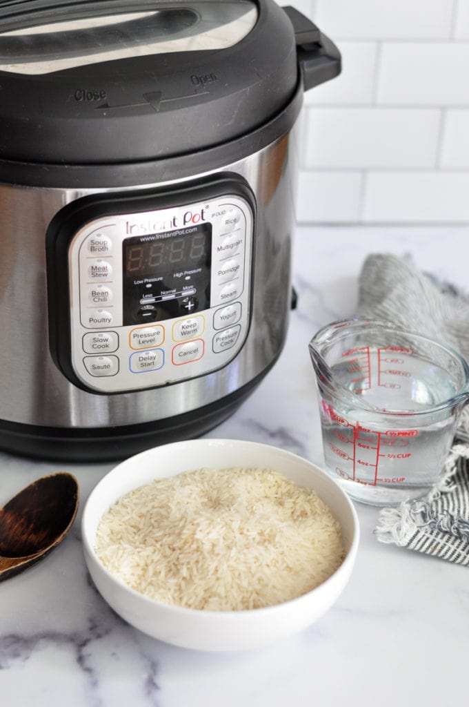 A bowl of uncooked jasmine rice, a cup of water, and an Instant Pot